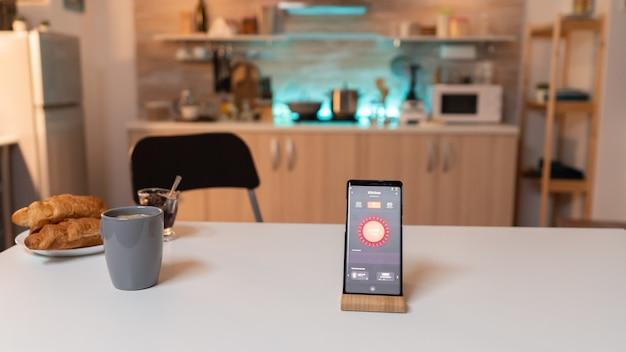Smartphone met smart home applicatie om de verlichting in huis aan en uit te doen. telefoon met aanraakscherm 's avonds laat met technologie om de lichten in huis te veranderen.