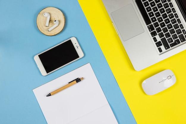 Smartphone met vel papier en oortelefoons