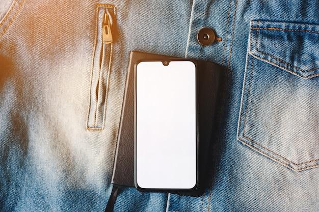 Smartphone met volledige schermweergave op de achtergrond van de jeans