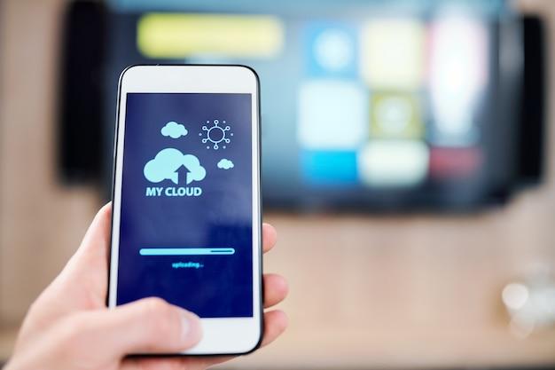 Smartphone met wolk- en zonpictogrammen en uploadlijn op display tijdens systeemaanpassing door mens