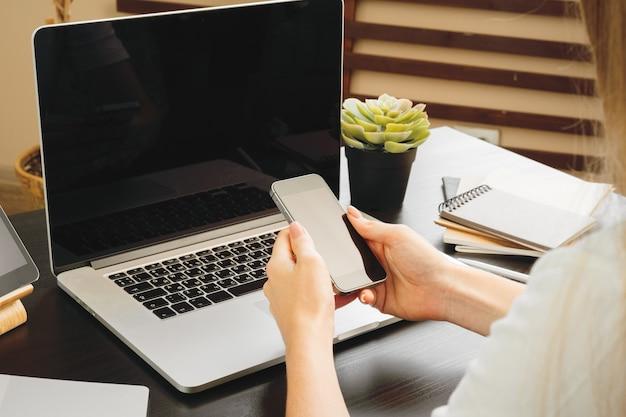 Smartphone met zwart scherm in vrouwelijke handen. computer-, toetsenbord- en kantoorbenodigdheden op een achtergrond