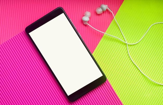 Smartphone-model met hoofdtelefoons tegen trendy veelkleurige achtergrond