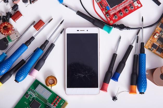 Smartphone, moederborden en hulpmiddelen die op witte achtertafel, radiotricianwerkruimte leggen. computerhardware, mobiele telefoon