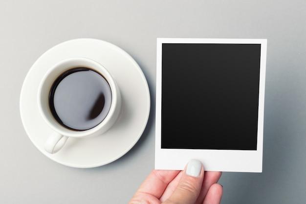 Smartphone naast van koffie op houten lijst.