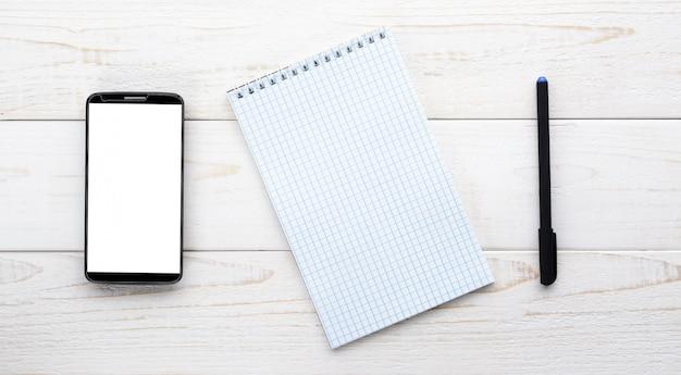 Smartphone, notebook met pen op een witte tafel