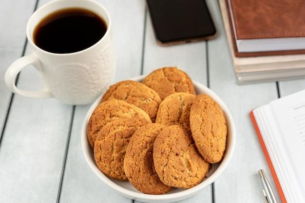 Smartphone, notitieboekje, pen, bord met koekjes en een mok zwarte koffie. bovenaanzicht van een werkplek op een houten tafel.