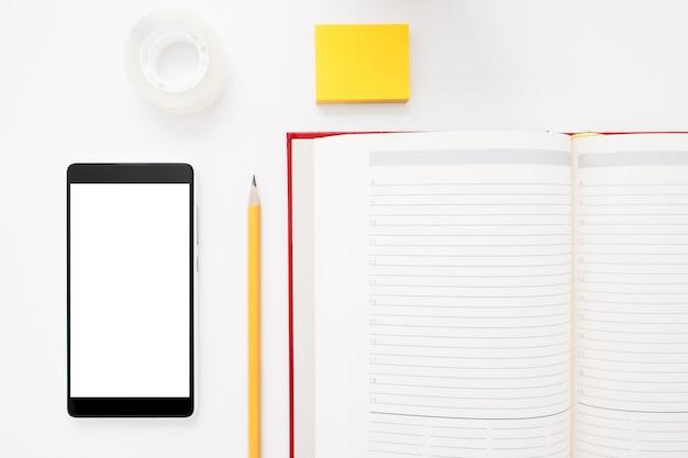 Smartphone, notitieboekje, potlood en stickers