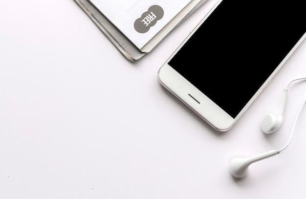 Smartphone, oortelefoon en tijdschrift op witte lijst met meer dan licht op de achtergrond