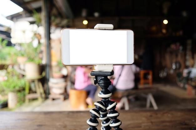 Smartphone op camerastatief en leeg scherm.