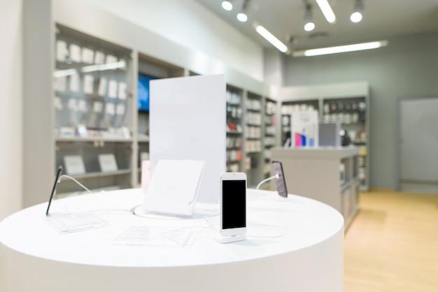 Smartphone op de achtergrond van een lichte technologie-winkel.