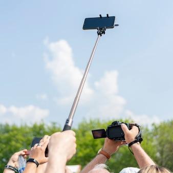 Smartphone op een selfiestok in mannelijke hand tegen de hemel.