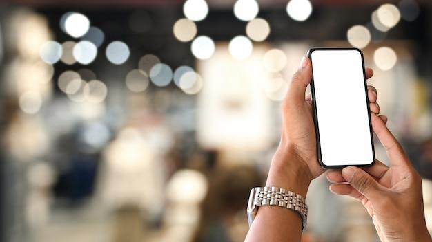 Smartphone op handen met het lege scherm en bokeh op nacht