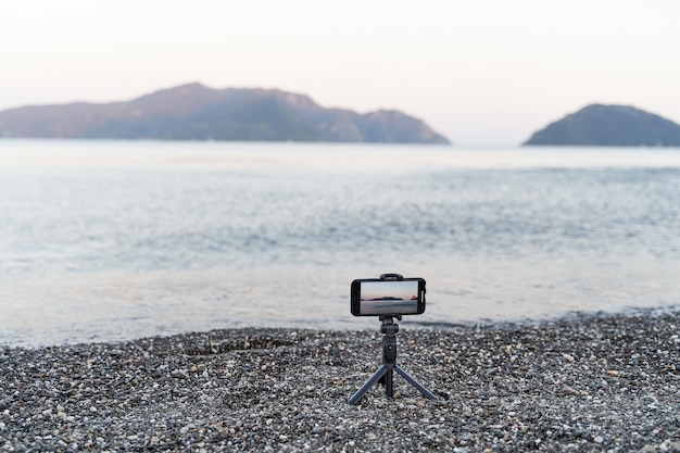 Smartphone op monopod-stick. video opnemen van zonsondergang op zee. content creator