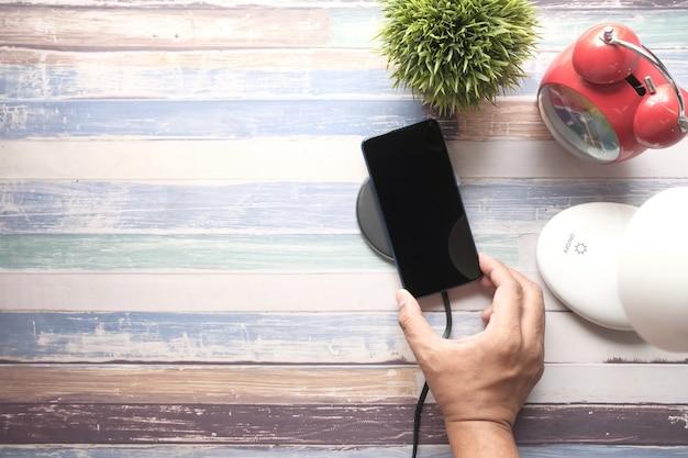Smartphone opladen met bovenaanzicht van draadloos oplaadstation