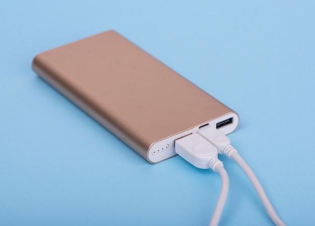 Smartphone opladen met powerbank op een blauwe achtergrond.