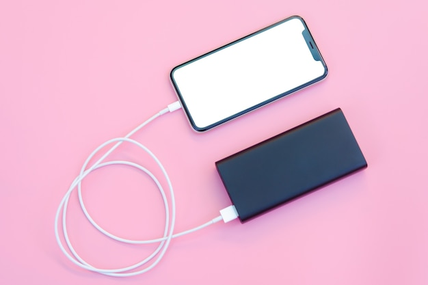Smartphone opladen met powerbank op roze achtergrond. wit scherm of leeg scherm met uitknippad voor kopieerruimte. plat leggen