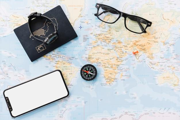 Smartphone; paspoort; polshorloge; kompas en bril op wereldkaart
