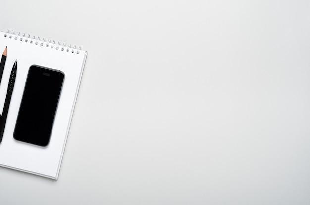 Smartphone, potlood, pen op een notitieblok op een grijze achtergrond.