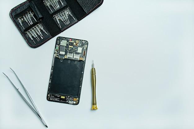 Smartphone reparatie. gedemonteerde smartphone, schroevendraaiers voor het demonteren van de telefoon. plat lag, bovenaanzicht. ruimte voor tekst.