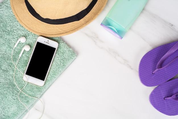 Smartphone, slippers, zonnebrandcrème en handdoek.