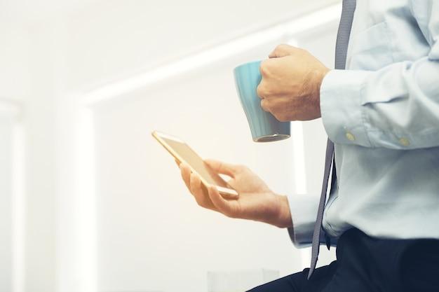 Smartphone ter beschikking van zakenman tijdens koffie-onderbreking die e-mail controleert