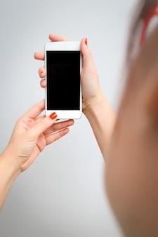 Smartphone van de de handgreep van de vrouw die het lege scherm bekijkt.