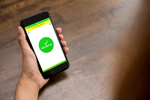 Smartphone van de handholding die met succes tekst voor taxi het boeken op het scherm tonen