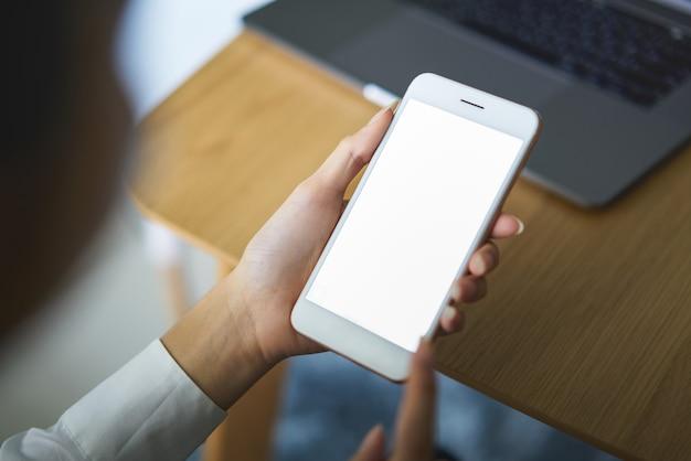Smartphone van de handholding met het lege scherm op lijst in koffie