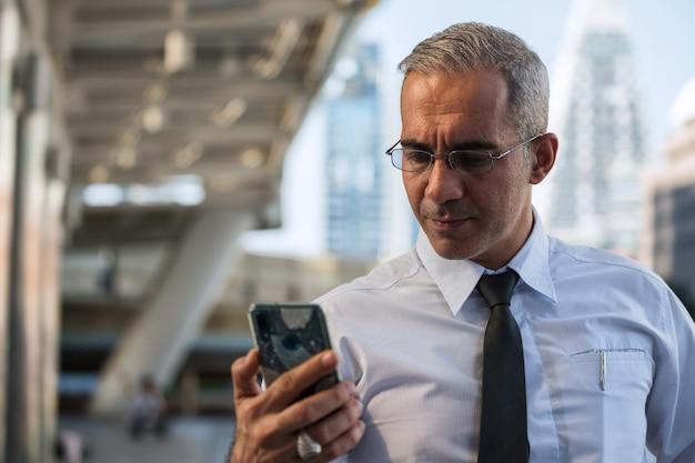 Smartphone van de jaren '50 amerikaanse zakenmancontrole in stad