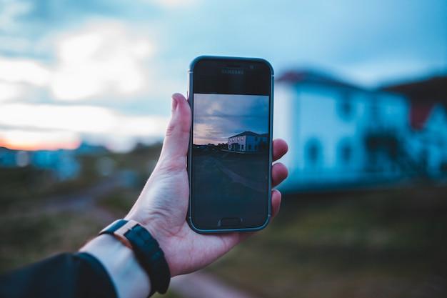 Smartphone van de mensenholding in zijn hand