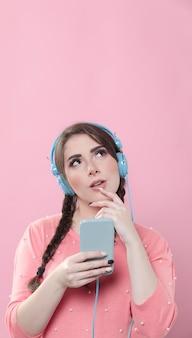 Smartphone van de vrouwenholding en het luisteren aan muziek op hoofdtelefoons