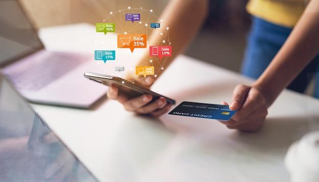 Smartphone van de vrouwenholding met online het pictogram en de kar van de pictogramkorting