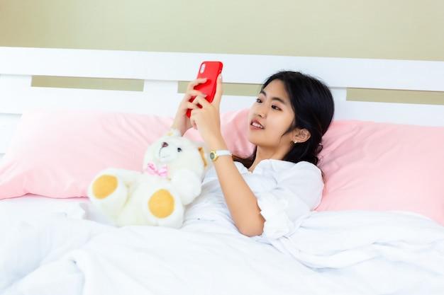 Smartphone van het tiener de vrouwelijke gebruik op het bed