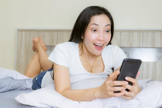 Smartphone van het vrouwen aziatische wauw gezicht op het bed