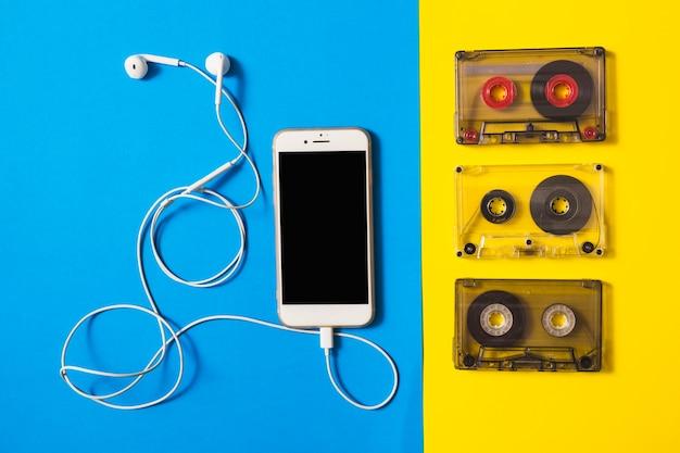 Smartphone verbonden met oortelefoon en cassettebanden op dubbele achtergrond