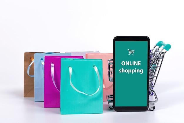Smartphone, winkelwagentje en kleurrijke papieren zakken geïsoleerd op een helder oppervlak, mockup voor ontwerp