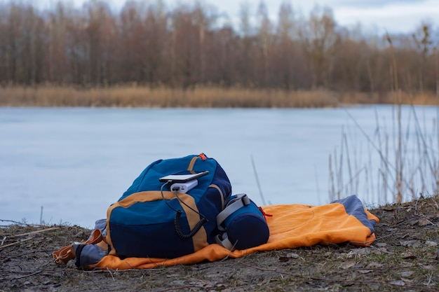 Smartphone wordt opgeladen met een draagbare oplader. power bank laadt de telefoon buitenshuis op met een rugzak voor toerisme op de achtergrond van de natuur en de rivier.