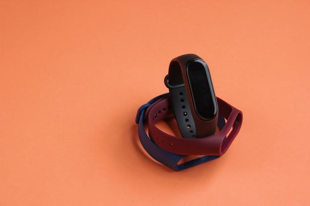 Smartwatch met verwisselbare armbanden op koraalkleurige achtergrond. fitnesstracker. moderne gadgets