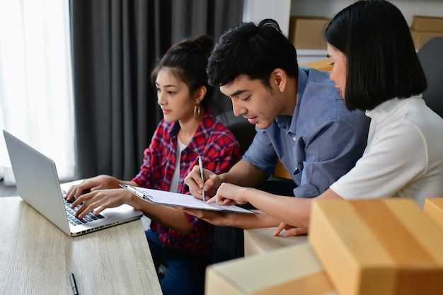 Sme bedrijfsconcept. jonge aziatische mensen pakken hun pakketten in.
