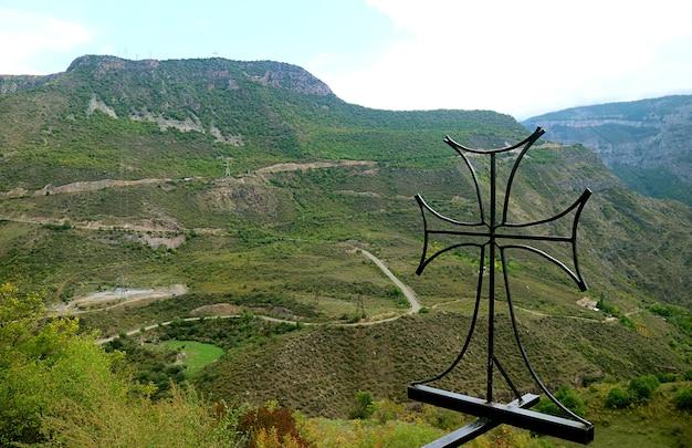 Smeedijzeren kruis tegen een prachtig panoramisch uitzicht op de bergen van de provincie syunik in armenië
