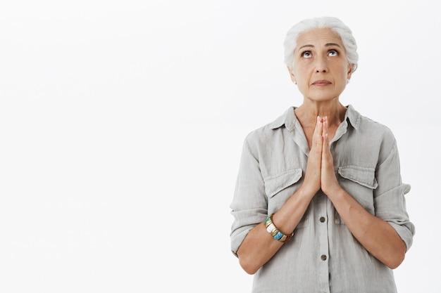 Smekende senior dame op zoek, hand in hand in gebed, smekend