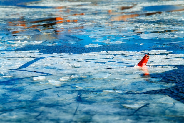 Smeltend ijs en rode boei op de achtergrond van het rivieroppervlak hd