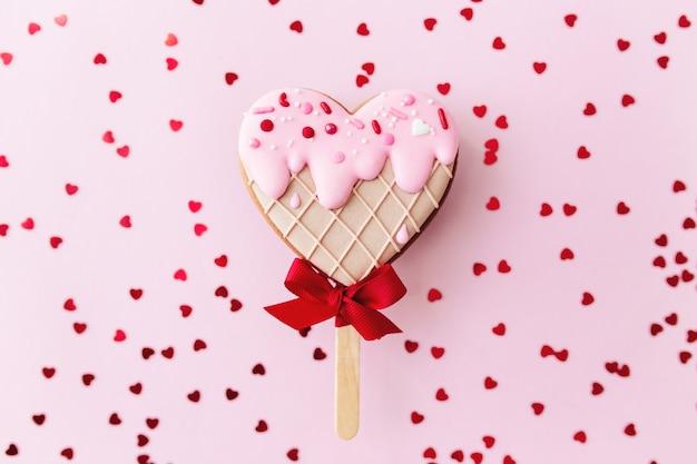 Smeltend ijs hart peperkoek cookie. valentijn. roze achtergrond, glitter. hoge kwaliteit foto