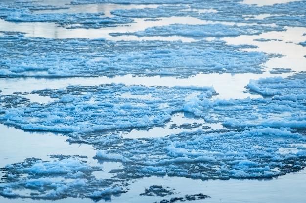 Smeltend ijs stroomt op het wateroppervlak. ijs drijft op de rivier