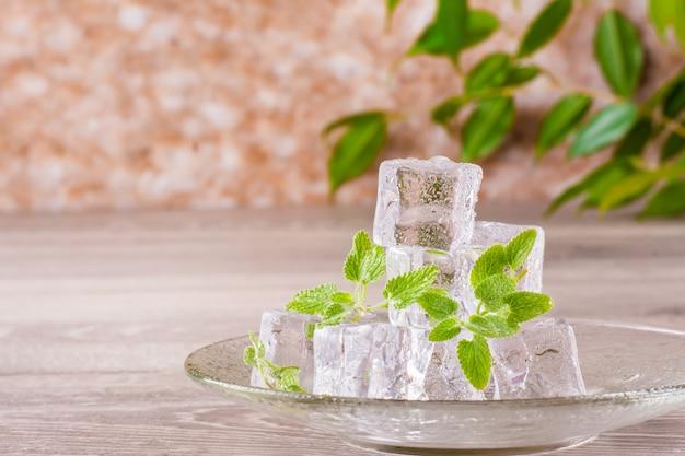 Smeltende ijsblokjes en muntblaadjes op een schotel op een houten tafel