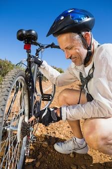 Smiing-fietser die zijn fietsketting op landterrein bevestigen