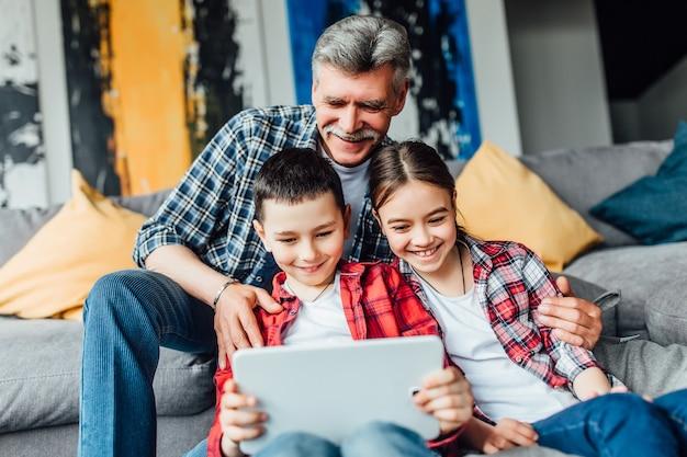 Smile broer en zus praten met moeder op laptop met hun opa in hun woonkamer.