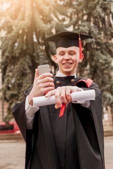 Smiley afgestudeerd jongen met mobiel