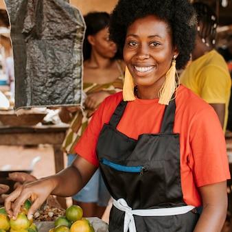 Smiley afrikaanse vrouw die op de markt werkt