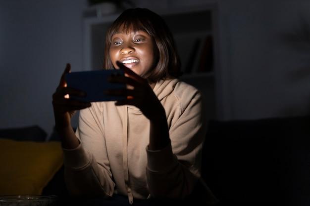 Smiley afro-amerikaanse vrouw kijken naar netflix thuis
